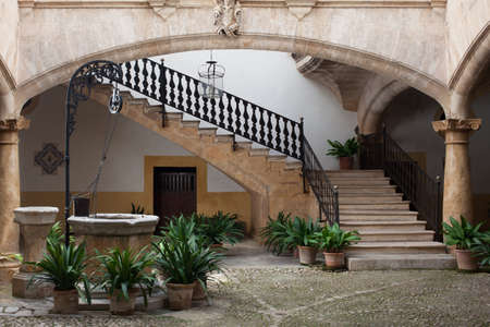 Cozy old european patio with well and stairs photo
