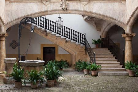 Gezellige oude europese patio met goed en trap Stockfoto
