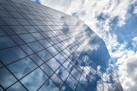 Modern building with reflection of blue sky and clouds photo
