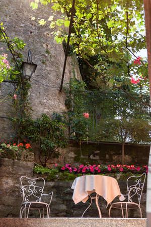 table and chairs in summer italian garden photo