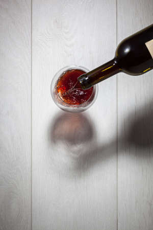 red wine pouring: Red wine pouring into glass from bottle on white wooden table. Top view