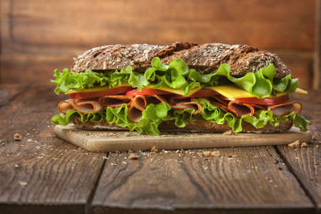 Sandwich on the wooden table with slices of fresh tomatoes, ham, cheese and lettuce