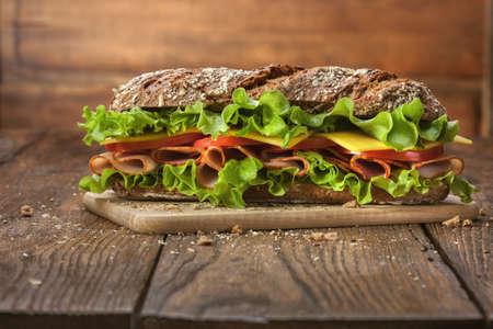 Sandwich op de houten tafel met plakjes verse tomaten, ham, kaas en sla Stockfoto