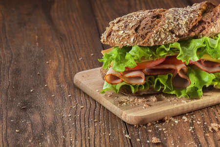 Deli: Sandwich on the wooden table with slices of fresh tomatoes, ham, cheese and lettuce