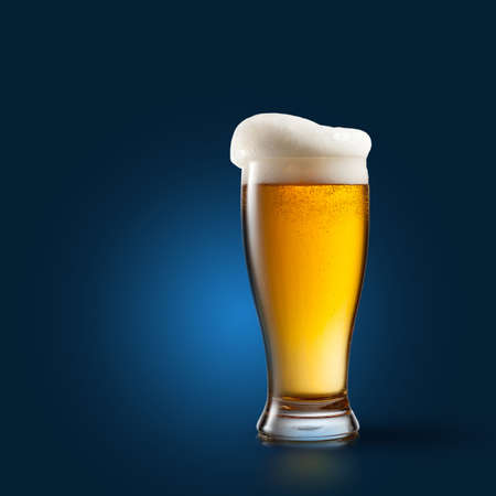 single beer: Beer in glass on blue background Stock Photo