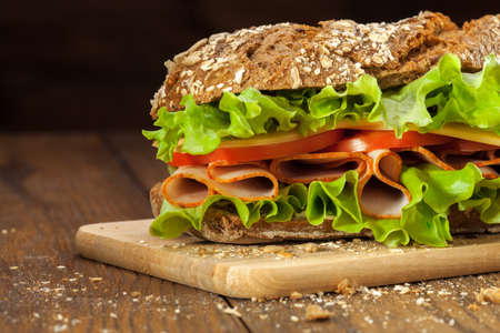 table grain: Sandwich on the wooden table with slices of fresh tomatoes, ham, cheese and lettuce