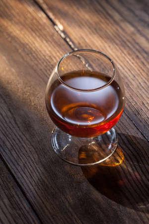 cognac: Cognac in glass on the wood