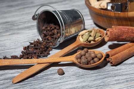 cardamon: Cardamon, clove and pepper in spoons on wood