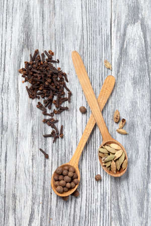 Nutmeg, clove and allspice in old spoon on wooden table photo