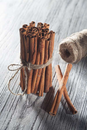 white backing: Cinnamon sticks isolated on white wooden table