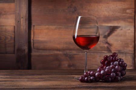 bebiendo vino: Vino rojo en vidrio con la uva en la madera