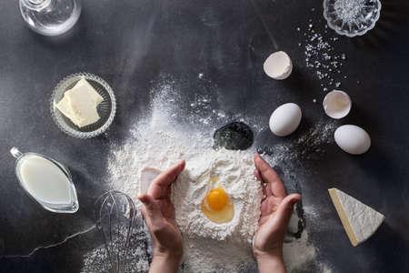 huevo: Manos de mujer amasan la masa en la mesa con harina