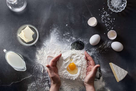 Woman hands knead dough on table with flour Imagens