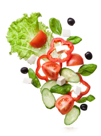 flying salad isolated in white - red tomatoes, pepper, cheese, basil, cucumber and olives