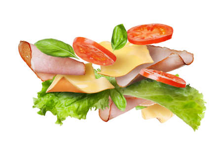 baguette: Ingredients for sandwich falling in the air isolated on white - slices of fresh tomatoes, ham, cheese and lettuce Stock Photo