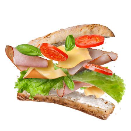 bocadillo: Sandwich con la caída de los ingredientes en el aire aislado en blanco - rodajas de tomates frescos, jamón, queso y lechuga