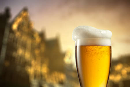 city light: Glass of beer against blurred european city Stock Photo