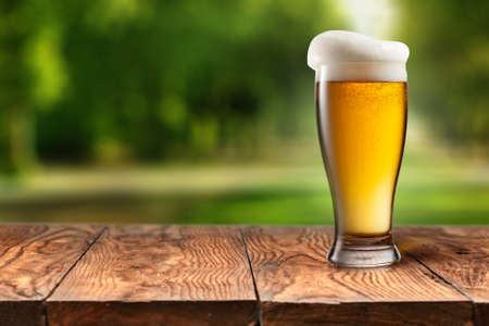mug of ale: Beer in glass on wooden table against park Stock Photo