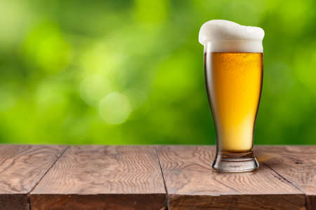 Beer in glass on wooden table against green