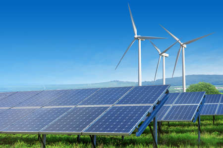 windmills: solar panels and wind turbines under blue sky Stock Photo