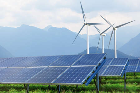 solar panels and wind turbines against mountains Standard-Bild