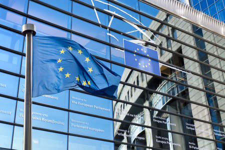 european: European Union flag against European Parliament Stock Photo