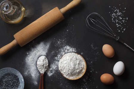 flour and ingredients on black table Imagens
