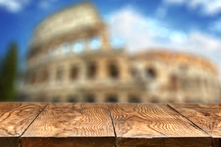 roman: Empty wooden table with Colosseum on background
