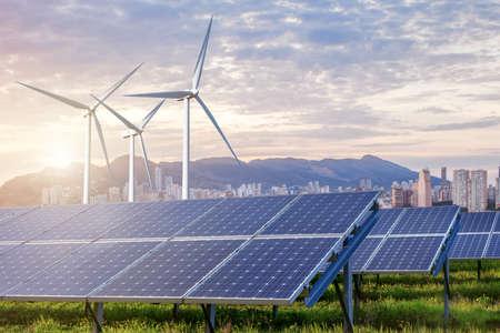 energia electrica: paneles solares y turbinas de viento bajo el cielo y las nubes con la ciudad en el horizonte. Salida del sol
