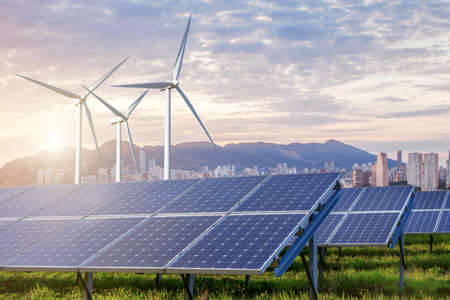 solar panels: solar panels and wind turbines under sky and clouds with city on horizon. Sunrise