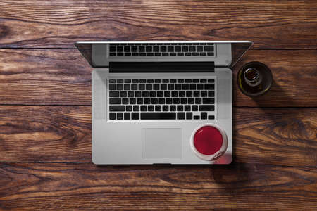 Open laptop and glass of red wine and bottle on brown wooden table. Top view