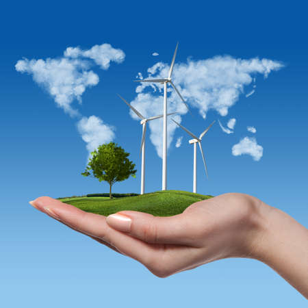 Wind turbines on meadow with tree holds in womans hand against blue sky and map of the world made of clouds. Worldwide Green energy concept