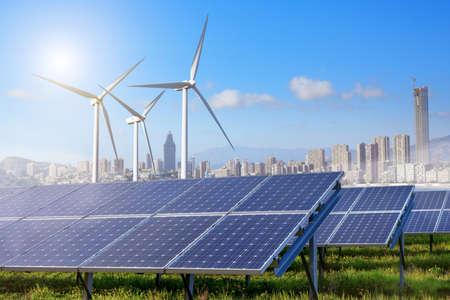 turbina: paneles solares y turbinas de viento bajo el cielo y las nubes con la ciudad en el horizonte. Salida del sol