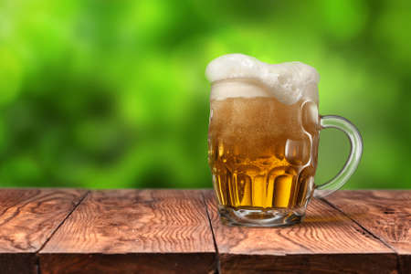 single beer: Beer in glass on wooden table with blurred green summer leaves on natural background with bokeh Stock Photo