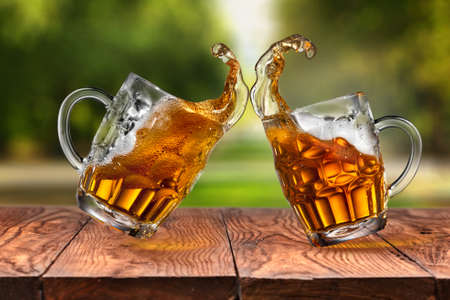 single beer: Splash of beer in two glasses on wooden table against blurred park on background