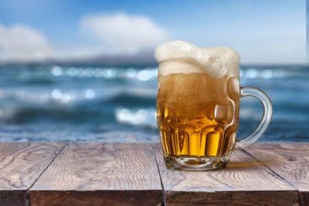 vasos de cerveza: Vaso de cerveza en la mesa de madera vacía con mar borrosa en el fondo, fondo natural con bokeh Foto de archivo