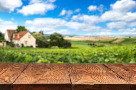 GRANJA: Mesa de madera vacía con el paisaje de viñedos en Francia en el fondo