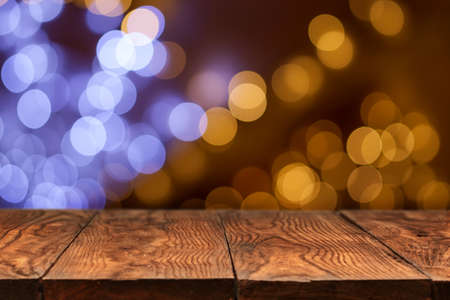 wood table: mesa de madera con luces de Navidad sobre fondo amarillo Foto de archivo