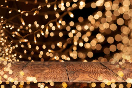 christmas illuminations: wooden table with yellow holiday lights on background