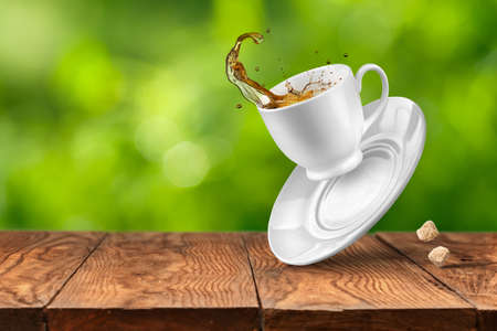 liquid splash: Splash of tea in the falling cup on wooden table against blurred green natural background