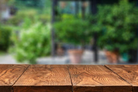 display: Empty wooden table against summer backyard or patio with green plants on background
