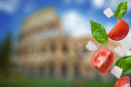 feta cheese: flying salad on colosseum on background - red tomatoes, pepper, cheese, basil, cucumber and olives Stock Photo