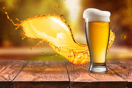 Beer in glass and splash on wooden table with blurred autumn city park on background, natural background with bokeh