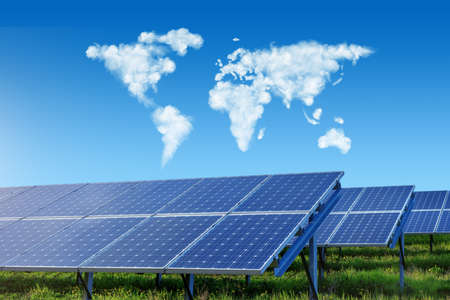 solar panels under blue sky with world map made of clouds Stockfoto