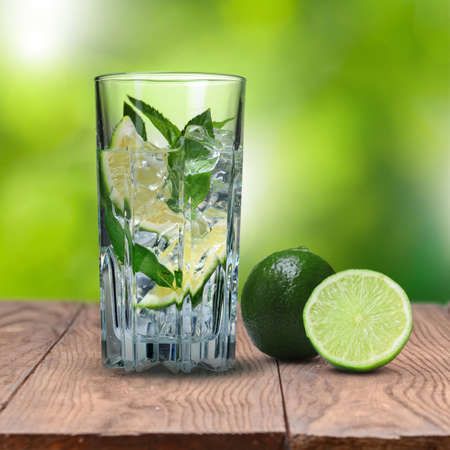 mohito: mohito cocktail with lime on wooden table against green natural background Stock Photo