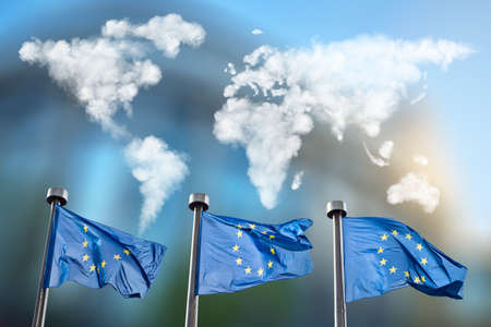 belgique: Flags of European Union with world map made of clouds against European Parliament in Brussels, Belgium