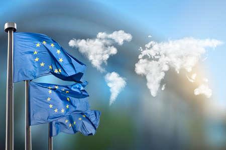 Drapeaux de l'Union européenne avec la carte du monde en nuages ??contre le Parlement européen à Bruxelles, en Belgique Banque d'images - 46144453
