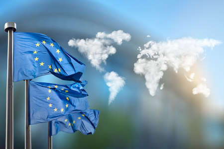 europeans: Flags of European Union with world map made of clouds against European Parliament in Brussels, Belgium