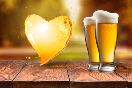 Beer in glass and splash in shape of heart on wooden table with blurred autumn city park on background, natural background with bokeh Foto de archivo