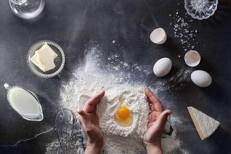 flour: Manos de la mujer amasan la masa sobre la mesa con harina, huevos y estropeaban. Vista superior.